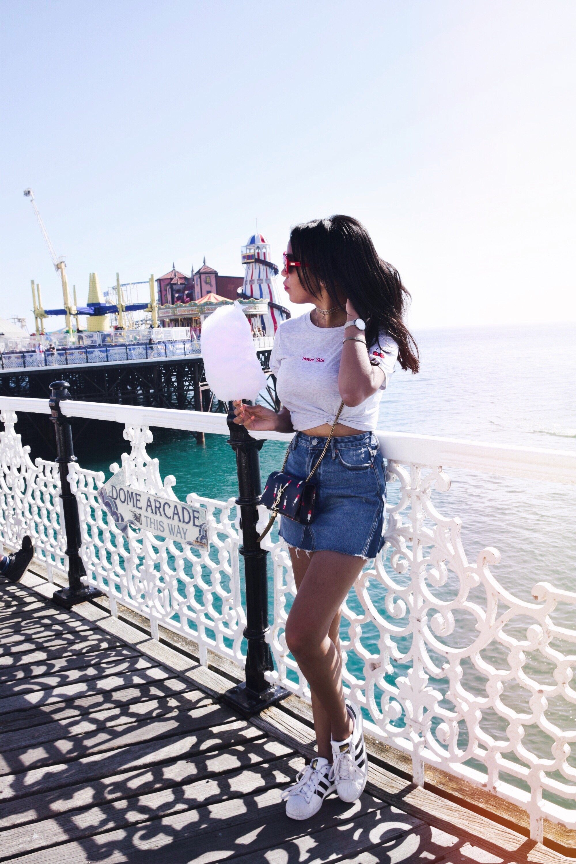 The Brighton Pier // Los Angeles Fashion Blogger Daphne Blunt // Brighton, England Summer Style // England Travel Diary Fashion Blogger // Saint Laurent Lipstick Bag YSL // GRLFRND Denim Skirt // Crap Eyewear Red Cateye Sunglasses // Adidas Originals // Topshop T-shirt: To Style, With Love